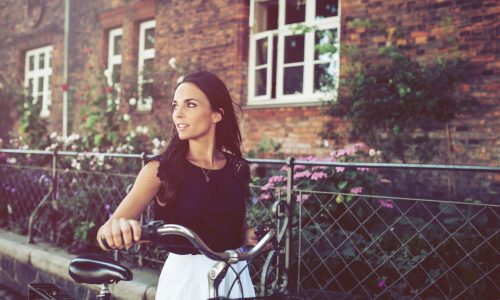 Outdoor shot of young woman walking along the road with a bicycle looking away. Woman with bike walking down the street in the city.